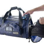 P7242 Firetech Deluxe Employee Gear Bag open person putting boots in bag.